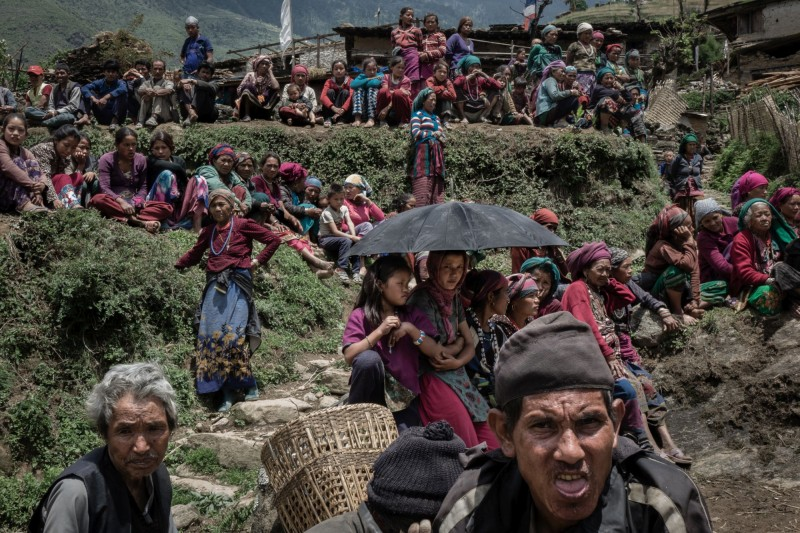 Villagers gather for the food distribution on hearing the sound of an arriving helicopter. (Pong Suracheth)