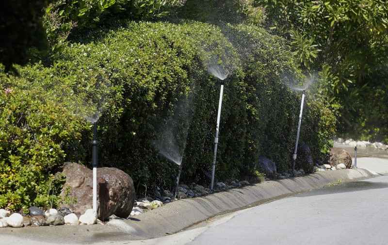 Water sprays from sprinklers outside of a home in Hillsborough, Calif., in April 2015. An emergency mandate has sought to limit outdoor water to conserve water, but the State Water Resources Control Board is considering making changes to it.