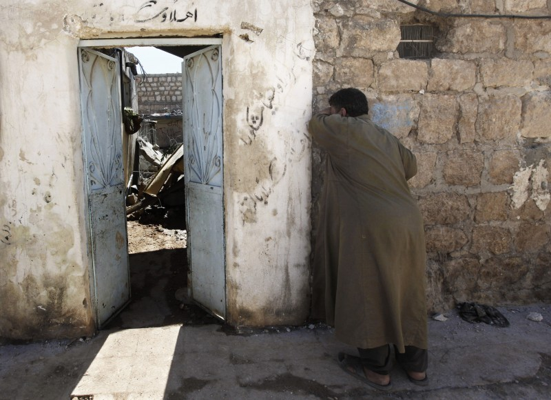 A man cries outside his destroyed home, hit by a government airstrike, in the village of Marea on the outskirts of Aleppo in September 2012. (AP Photo/Hussein Malla)