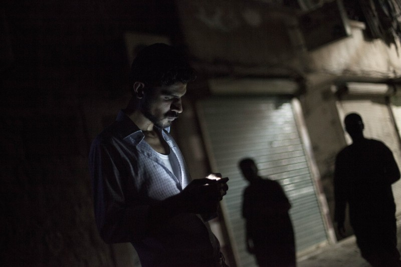 A man looks at his mobile phone in the Bustan al-Qasr neighborhood of Aleppo in Septmber 2012. (AP Photo/ Manu Brabo)