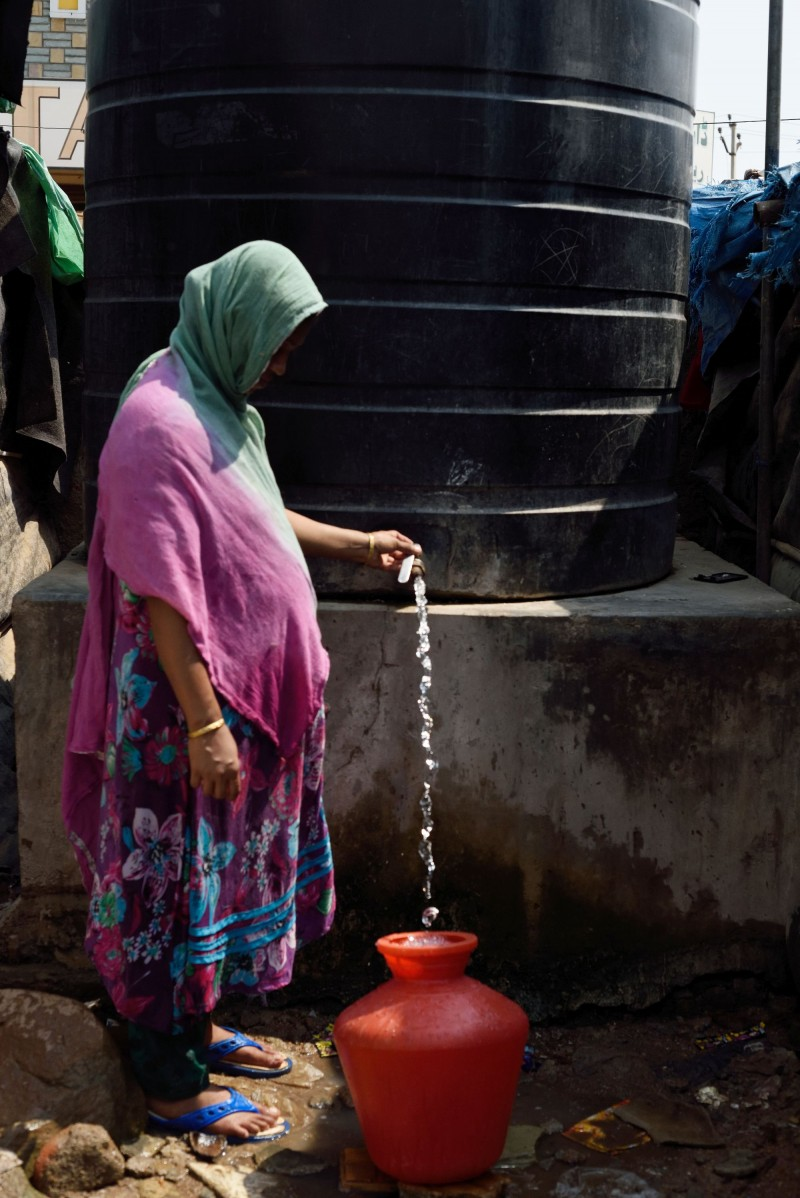 With the onset of summer and the lack of rain, water woes are compounded. Here a woman from the camp drains water from the community tank. (Kashif Ali)