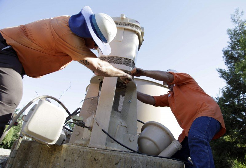 Dennis Hall, left, and Micha Berry with the city of Fresno's water division, unscrew the motor that sits on top of a groundwater well to repair the well's pump, in Fresno, Calif. Fresno has for decades relied exclusively on groundwater as a drinking water source for its residents. (Gosia Wozniacka, Associated Press)