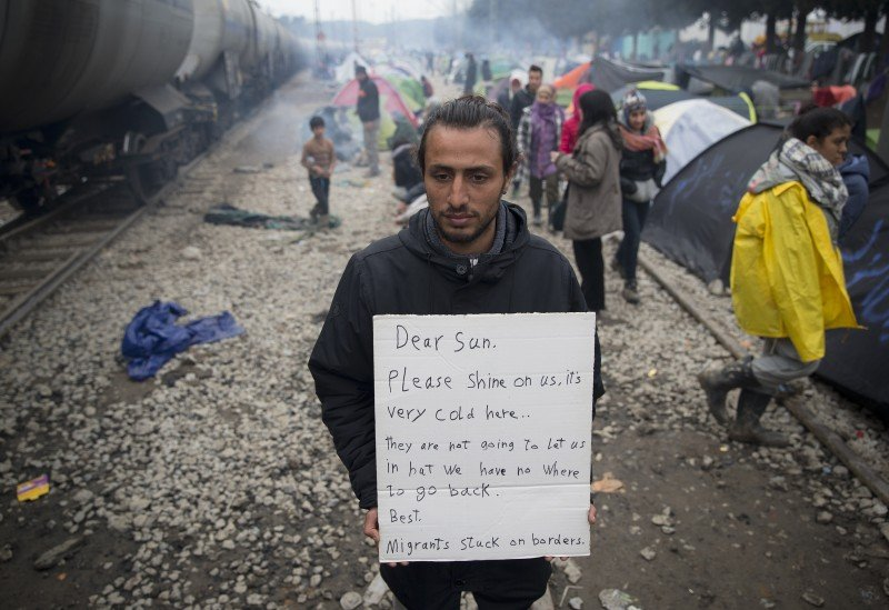 A man holds a handwritten sign near tents set up beside railway tracks at the northern Greek border point of Idomeni. (AP Photo/Vadim Ghirda)