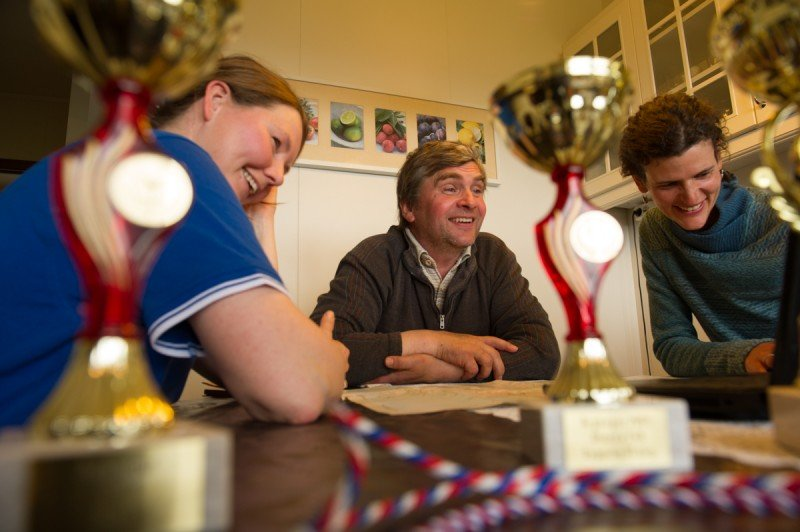 Lauga, Eyberg and Jennifer Kingsley share stories amid farming trophies spread across the kitchen table. (Eric Guth)