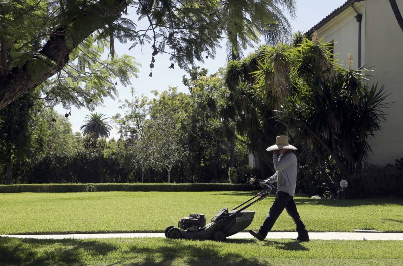 A gardener mows a lawn in Pasadena, California. The State Water Resources Control Board may soon lift last year's water conservation mandate. (Nick Ut, Associated Press)