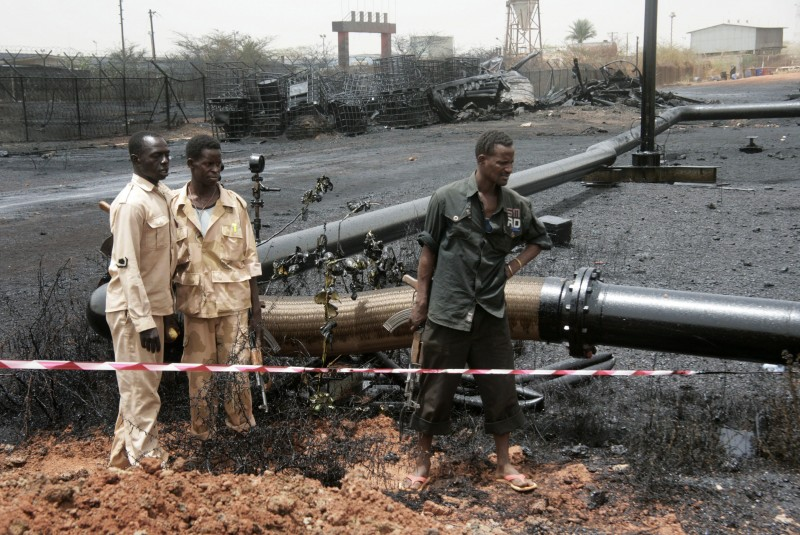 In this Tuesday, April 24, 2012 photo, Sudanese armed forces stand near burnt oil pipes at the oil-rich border town of Heglig, Sudan. The African Union says Sudan must stop the aerial bombardment of South Sudan and has called on both countries to cease hostilities immediately. (AP Photo/Abd Raouf)