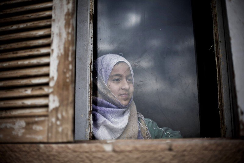 A Syrian girl from Aleppo looks outside a window of an abandoned building where her family and several others took refuge due to fighting between Free Syrian Army fighters and government forces on Feb. 28, 2013. (AP/Manu Brabo)