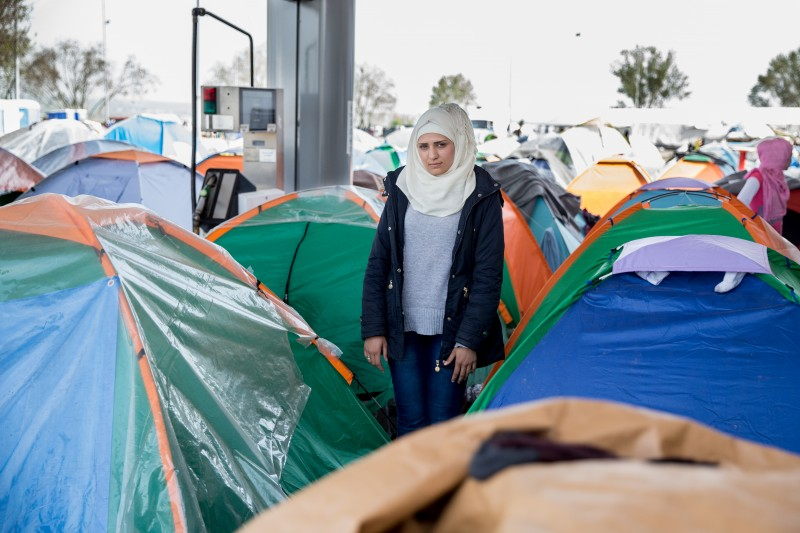 "Rahaf Habash, 21, stands next to her small tent near a crowded gas pump. She was married to her husband Basel for fewer than four months when he left their home outside Damascus for Germany. She followed him in February and was forced to give up most of her belongings and valuables as bribes to various Syrian authorities when she crossed into Turkey, including her wedding ring. Except for friends, she is alone at EKO camp. ""Where are the human rights? Where are the children's rights? It's shameful, isn't it?"" she says of conditions in the camp. (Kelly Lynn Lunde)"
