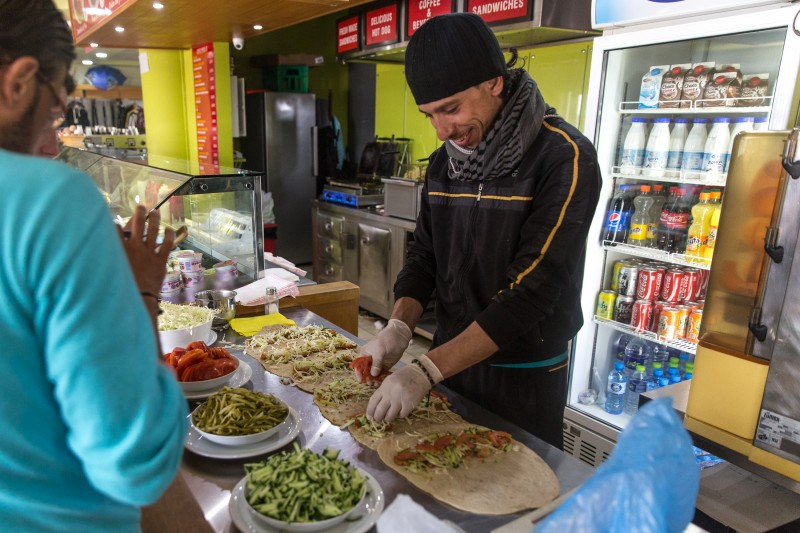 A Syrian prepares falafel in the gas station cafe. The owners allow the former chef to make and sell his street food from the cafe's kitchen for 1 euro a piece, using bread prepared by other refugees in the camp. With limited food distribution by MSF, the falafel provides a relatively cheap and familiar meal for residents who can afford it. (Kelly Lynn Lunde)
