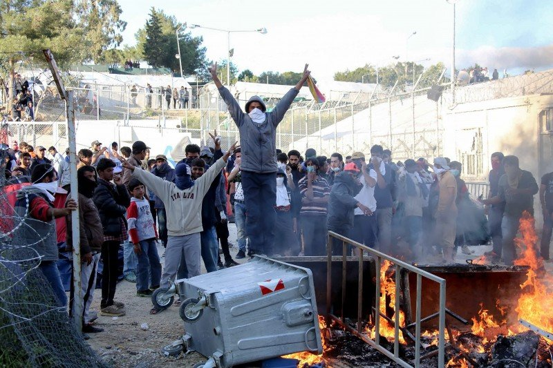 Migrants make a victory sign as garbage bins burn at the Moria migrant detention center on the northeastern Greek island of Lesvos. (Petros Tsakmakis/InTime News via AP)