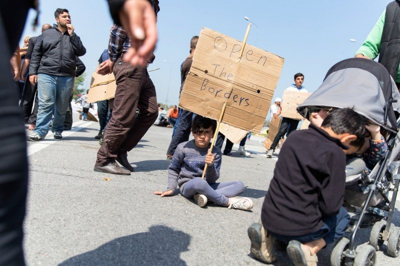 A boy holds a sign on April 4, 2016 on the third day of protest along the highway outside Polykastro, in Central Macedonia, Greece. (Kelly Lynn Lunde)