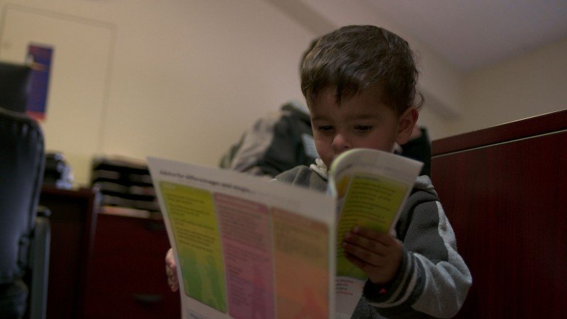 Shadi looks at the Canadian Food Guide during his family's first meeting with a settlement counselor. (Asha Road, 19 Days)