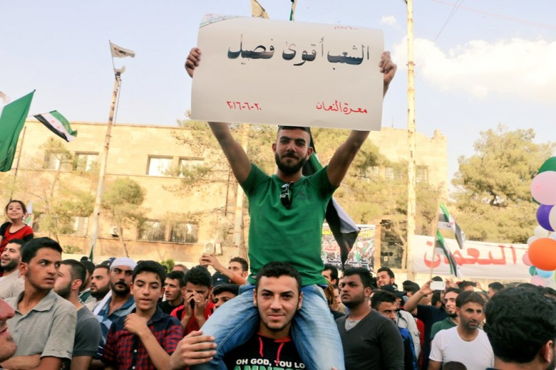 A young man holds a placard during one of the peaceful protests organized in Maarat al-Numan that says, 'The people are the strongest faction'. June 20, 2016. (Anonymous)