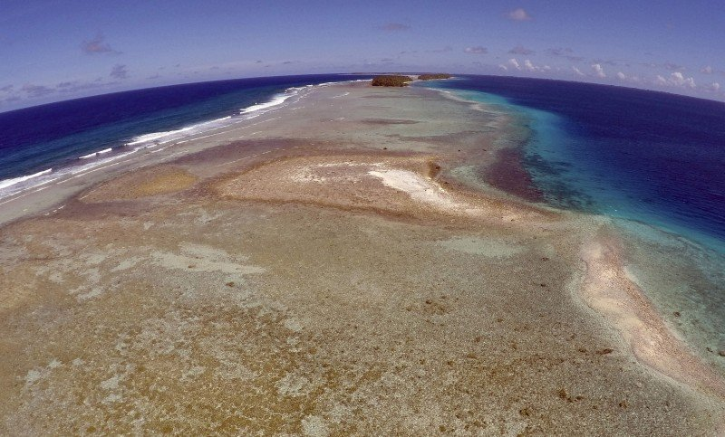 FILE - In this Thursday, Nov. 5, 2015 file, aerial photo a small uninhabited island that has slipped beneath the water line only showing a small pile of rocks at low tide on Majuro Atoll in the Marshall Islands. They barely break the surface of the ocean but in the U.N. talks on how to stop rising seas and other hazards of a warming planet, small island nations have the moral high ground. While most countries think of climate change in terms of economic costs, Pacific atolls and remote island groups in the Indian Ocean and Caribbean picture a world map without them on it. Rising seas are already eroding their coast lines and contaminating their freshwater wells. Many are in the path of typhoons and hurricanes that scientists say could become more powerful as the climate warms. (AP/Rob Griffith, File)