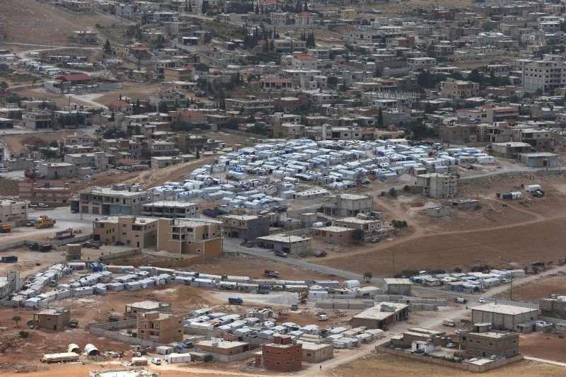 This Sunday June 19, 2016 photo shows several Syrian refugee quarters in the foreground, and the town of Arsal, near the Syrian border, in northeast Lebanon. (AP/Hussein Malla)