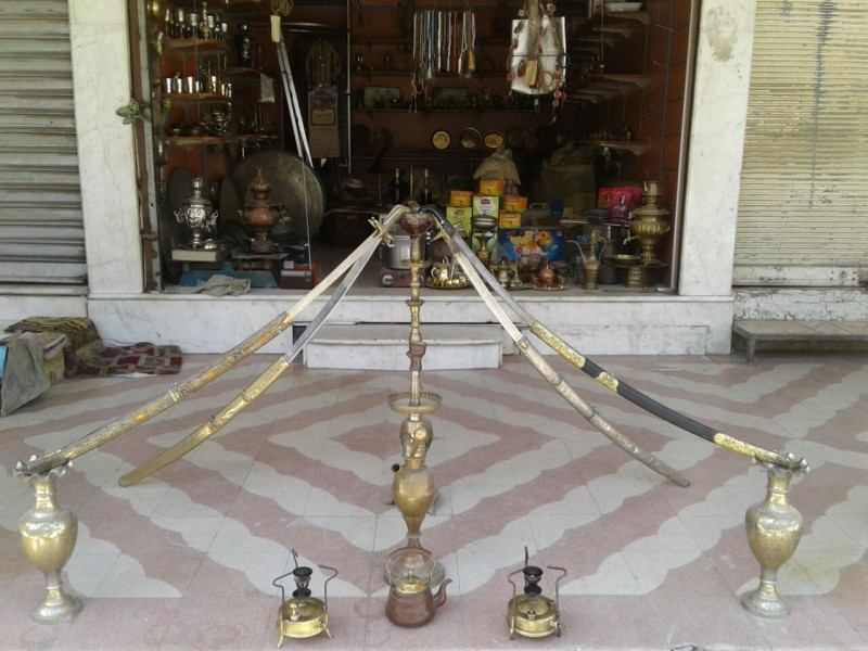 A 100-year-old hookah bowl with four ancient swards on display in front of Abu Abdo's shop. Eastern Ghouta, June, 2016. (Syria Deeply)