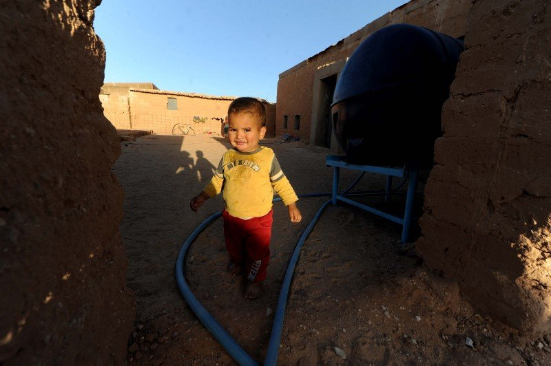 A child stands at one of the few water resources in the community. (AP/Toukik Doudou).