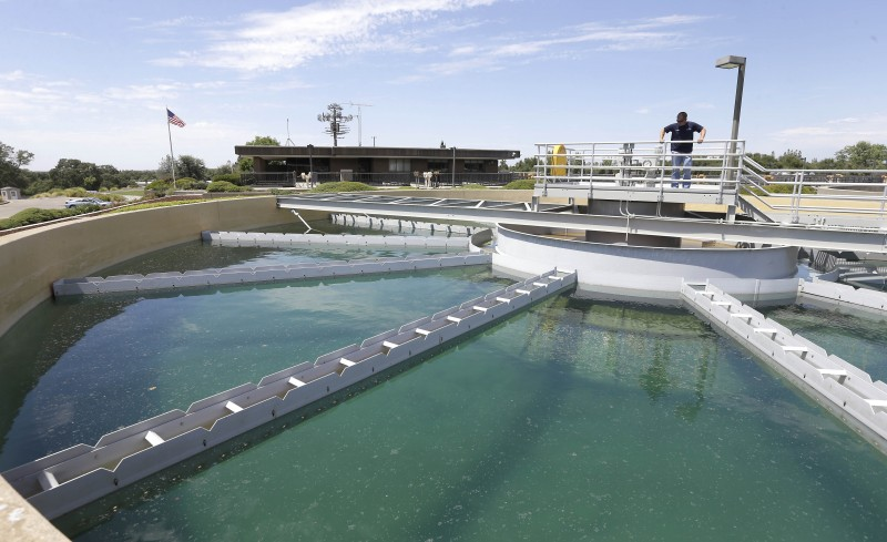 """Dan Johnson, a treatment plant operator, inspects a sediment pond at the Roseville Water Treatment Plant in Granite Bay, Calif., in July 2015. Due to reduced water use, Roseville is among the water agencies that have had to impose a """"drought surcharge"""" in order to make up the lost revenue. (Rich Pedroncelli, AP)"""