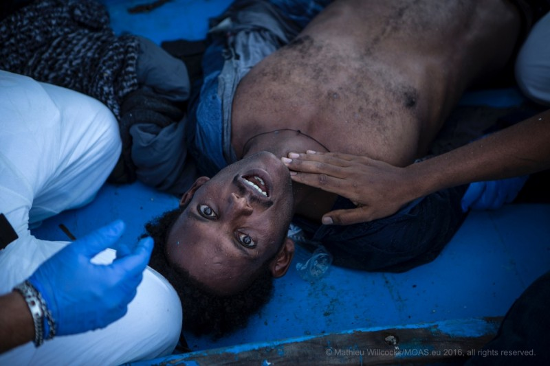"""A man gasps for breath and is eventually revived. But four of his co-passengers did not make it. Human rights organizations equate the conditions prompting flight of Eritrean civilians with """"slavery."""" (MOAS/Mathieu Willcocks)."""