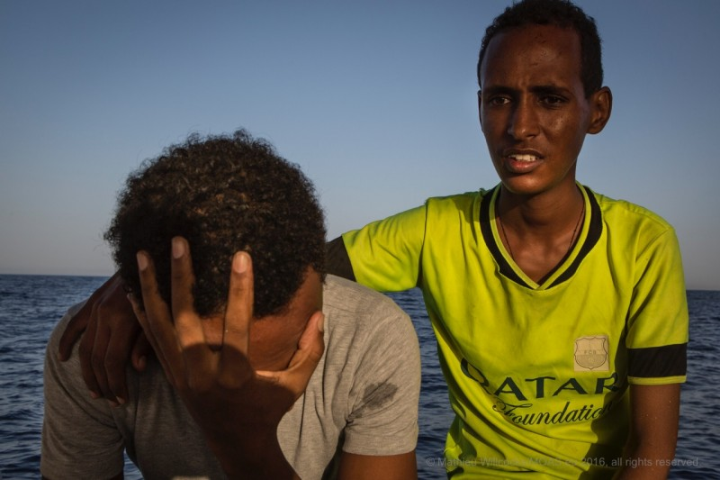 Rescued men grieve the loss of their friends' lives. Numerous reports have cited torture, mass surveillance and indefinite military conscription of civilians by the Eritrean government. (MOAS/Mathieu Willcocks)