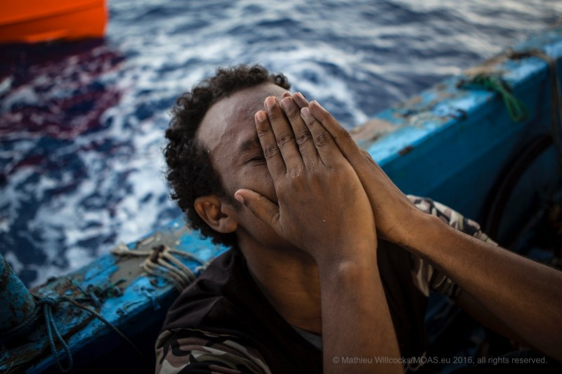 A rescued man cries out in both relief and sadness.Over 200,000 asylum seekers of different nationalities have reached Italian shores this year. (MOAS/Mathieu Willcocks)
