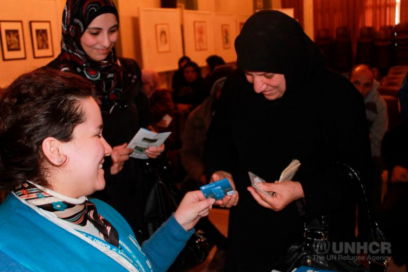 Fatima and Oula (mother and daughter) receive ATM cards from a UNHCR official in Tripoli, north Lebanon. (UNHCR)