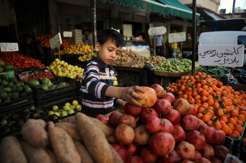 Eight-year-old Mohammed Hassan, who fled with his family from Idlib, Syria, sells fruits at a market in the Palestinian refugee camp of Sabra in Beirut, Lebanon. Research indicates that families receiving cash assistance are less likely to send their children to work. (AP/Bilal Hussein)
