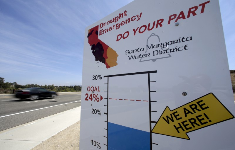 Cars in Rancho Santa Margarita, California, drive by a sign encouraging residents to save water. California lifted its statewide water conservation mandate in June 2016, but some think some level of conservation by water suppliers is still needed. (Chris Carlson, AP)