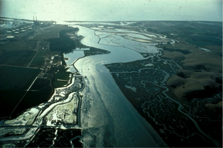 Aerial photo of Elkhorn Slough, looking west toward Moss Landing and Monterey Bay. The Deep Water Desal facility is proposed on the property in the upper left where an old crude oil storage tank farm was once located. (Moss Landing Marine Laboratories/California State Universities)