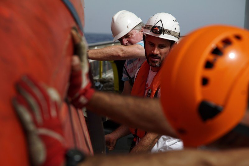 MSF and the rescue group SOS Mediterranee crew carry a small boat during a training exercise on the Aquarius vessel, in the Mediterranean Sea. (AP/Bram Janssen)