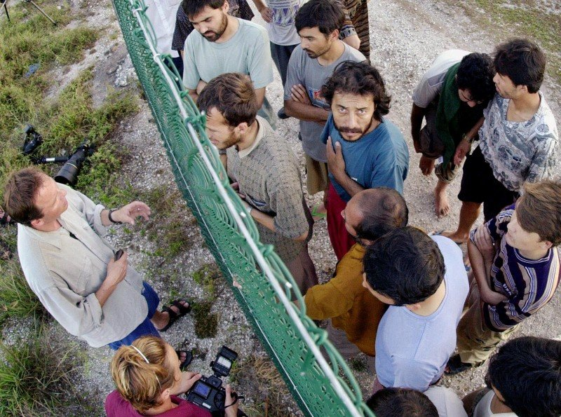 Refugees gather on one side of a fence to talk with international journalists about their journey that brought them to the Island of Nauru. The South Pacific island nation has become an immigration detention and offshore asylum processing centre for Australia. (AP/Rick Rycroft)
