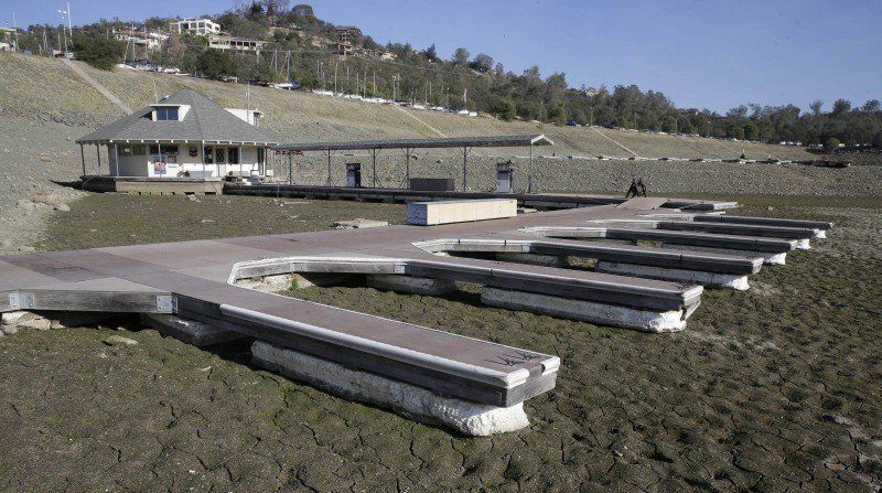 In this Nov. 17, 2014 file photo, boat slips sit on the dry lake bed at Brown's Marina at Folsom Lake, near Folsom Calif. Global warming worsened record droughts in California. (Rich Pedroncelli, AP)