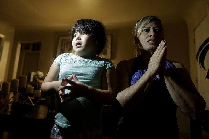 Yaritza Pizano, 4, left, prays alongside her grandmother, Maria Marquez, at their home in the community of Okieville, on the outskirts of Tulare, Calif. As Yaritza's family began to run out of available water in 2014, she started praying for it during her nightly prayers. (Edit image Image title: California Drought Dry Town Image caption: SECOND IMAGE - Yaritza Pizano, 4, left, prays alongside her grandmother, Maria Marquez, at their home in the community of Okieville, on the outskirts of Tulare, Calif. As Yaritza's family began to run out of available water in 2014, she started praying for it during her nightly prayers. (Gregory Bull, AP)