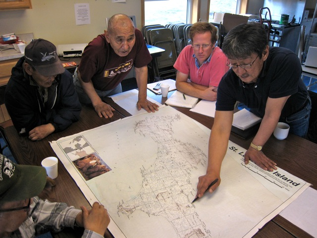Henry Huntington (pink shirt) interviews people from the community of Savoonga, Alaska about the subsistence hunt. (Henry Huntington)