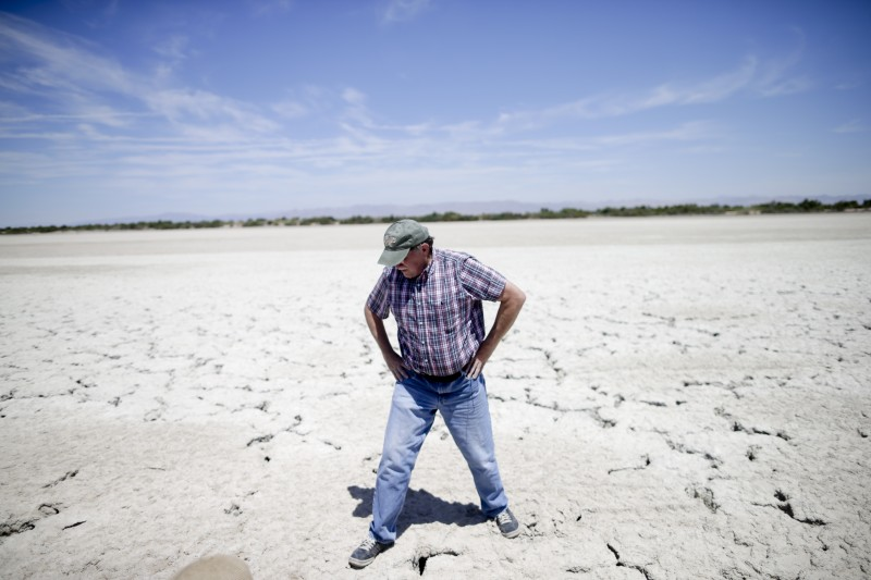 Bruce Wilcox of the Imperial Irrigation District looks down at the cracked, exposed Salton Sea lakebed near Niland, Calif. The lake's shrinkage has exposed about 25 square miles (65 square kilometers) of salt-encrusted lakebed since 2003, with more likely to come. (Gregory Bull, AP)