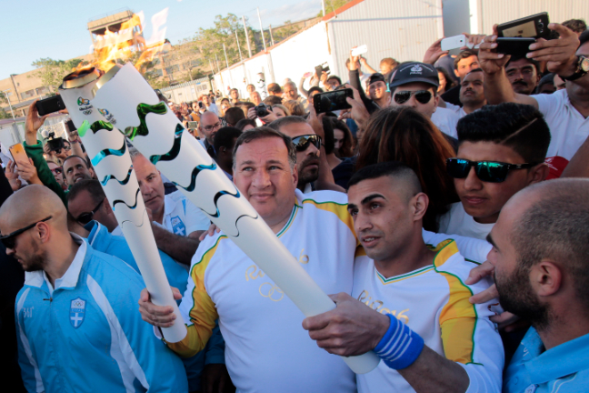 Ibrahim al-Hussein lights the Olympic torch as the relay came to the refugee camp in Elaionas, outside Athens. (Milos Bicanski)