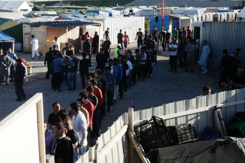 Men queue up to receive their daily food distribution in a makeshift camp in Calais. Tempers are rising among migrants squeezed in record numbers into a shrinking 'slum' in France's port city. (AP/Michel Spingler, File)