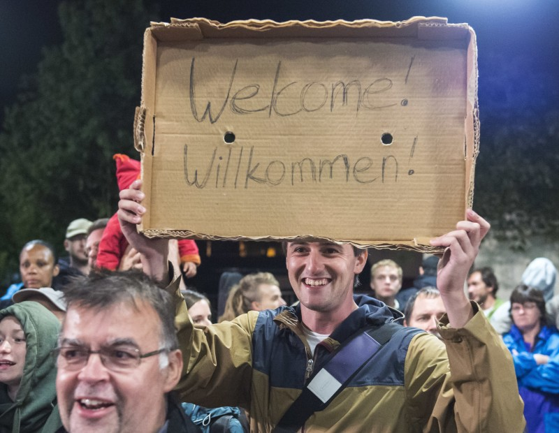 "A man holds a piece of cardboard with a ""Welcome"" slogan during the arrival of refugees at the train station in Saalfeld, central Germany. (AP/Jens Meyer,file)"