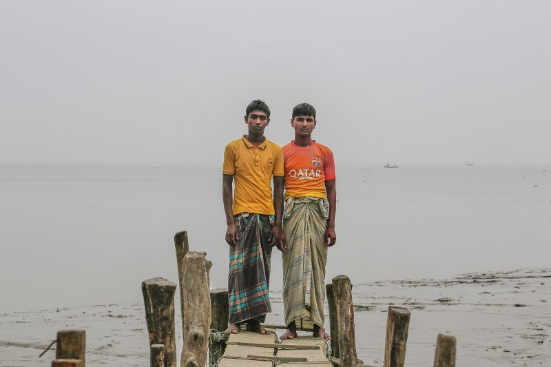 Two brothers, Ashikur, 24 (right), and Arifur, 21, stand in the spot where their home was once located, in the island district of Bhola, Bangladesh. (AP/Shahria Sharmin)