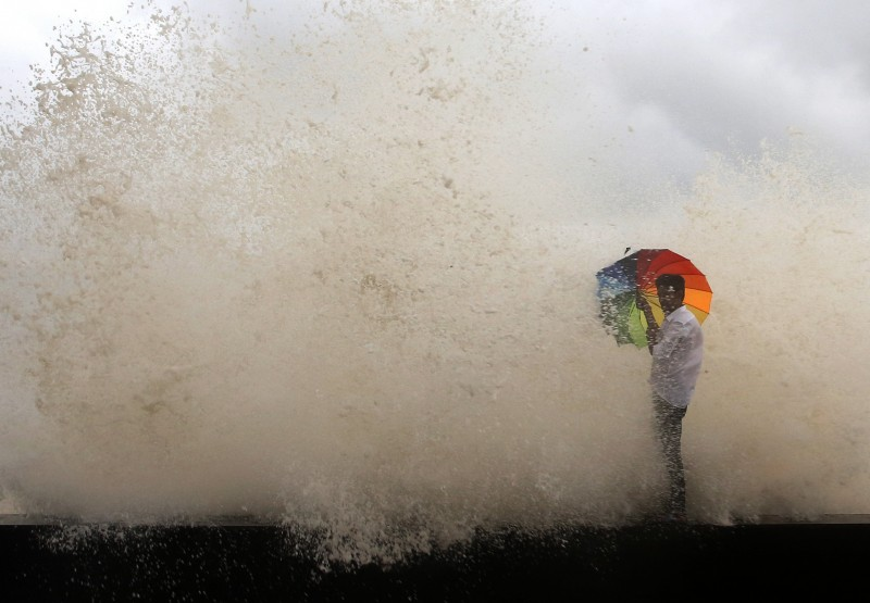 A man holds an umbrella as water engulfs him during high tide on the Arabian Sea coast, in Mumbai, India. A new study by the journal Science Advances shows that man-made climate change is responsible for most of the change seen in ocean surface temperatures near the equator, which in turn affect regional rainfall patterns, including the Indian monsoon. (AP/Rajanish Kakade )