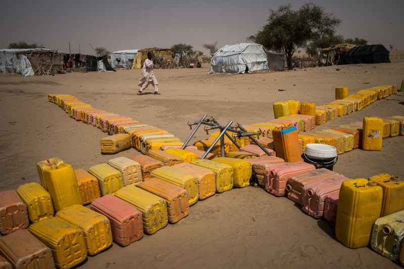 Water bottles are laid in a line in the Sayam refugee camp, Niger. Sayam houses about 4,000 people in a remote area far from any facilities. Although there is no fence, the army patrols the area. Vincent Tremeau/Oxfam
