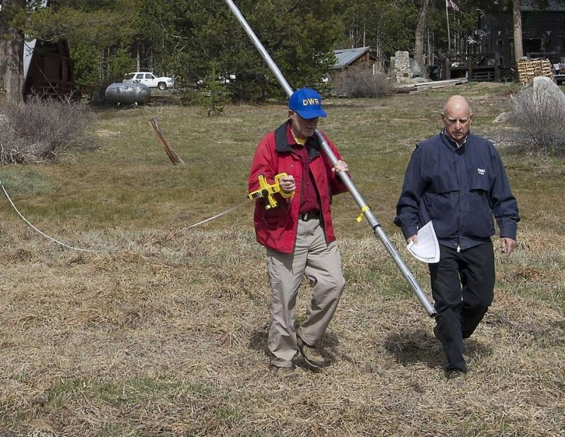 Gov. Jerry Brown, right, walks into a snowless meadow during the 2015 snowpack survey. The lack of snow bolstered the governor's case for water conservation. This year it's unknown whether the winter will be wet or dry. (Randall Benton, Sacramento Bee)
