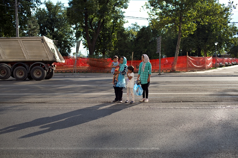 """Thirty-six-year-old Marzia, far left, holding her youngest daughter, walks with her two other daughters toward Belgrade's """"Afghan Park"""" after receiving food from a distribution center. (Danielle Villasana)"""