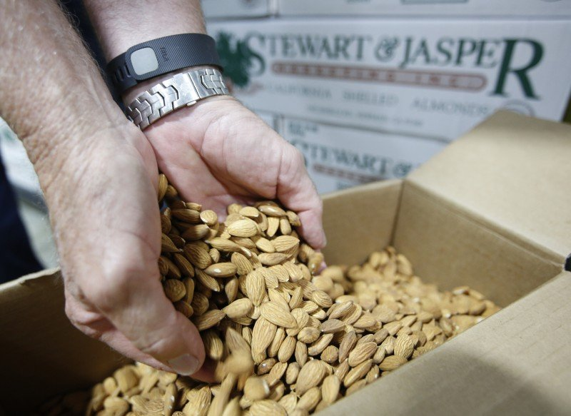 In this Tuesday, July 21, 2015 photo, Jim Jasper, owner of Stewart Jasper Orchards, displays a box of almonds that are ready for shipping at his processing plant in Newman, Calif. Almonds are catching the eye of investors in California despite the recent drought. (Rich Pedroncelli, AP)