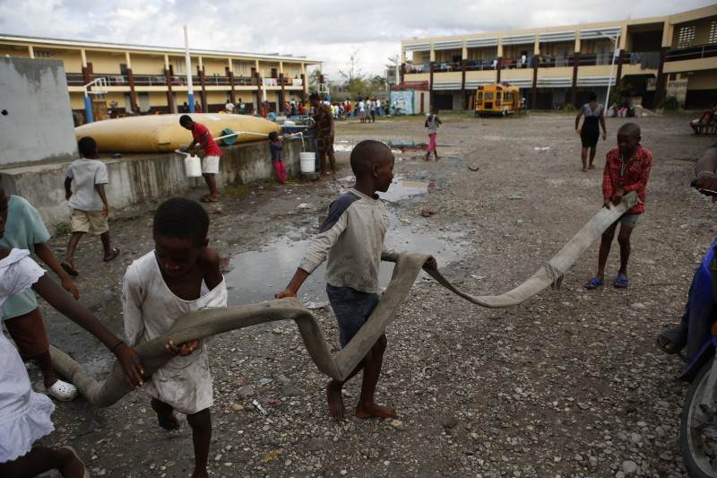 Boys whose homes were destroyed by Hurricane Matthew carry a hose from a water tanker truck at Philippe Guerrier High School in Les Cayes, Haiti. (AP/Rebecca Blackwell)