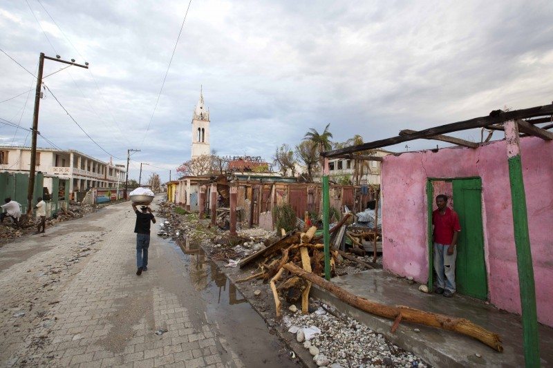Clony Toussaint stands in the doorway of his home, damaged by Hurricane Matthew, in Port-a-Piment, a district of Les Cayes, Haiti. Government personnel and an army of international aid workers are delivering more relief supplies to people, but local authorities say it is falling well short of meeting desperate needs. (AP/Dieu Nalio Chery)