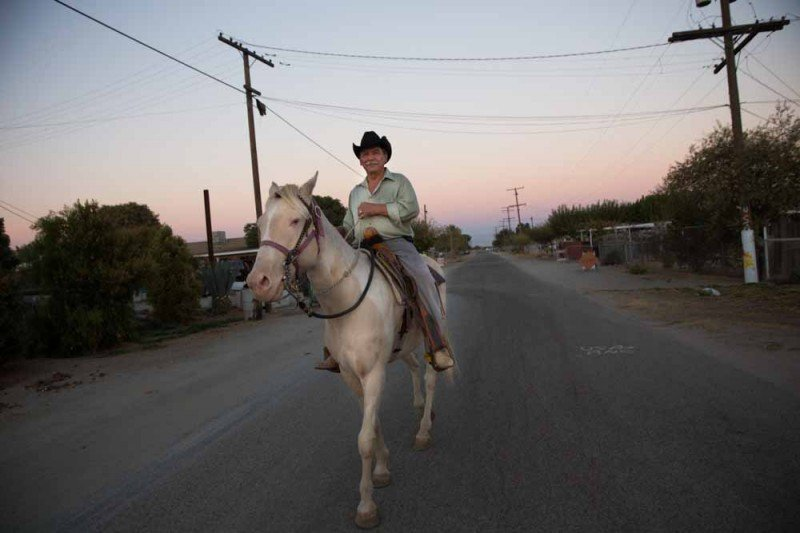 A resident of the hamlet of Okieville, California (also called Highland Acres) in rural Tulare County, is out for an evening ride on his horse. (Sarah Craig)