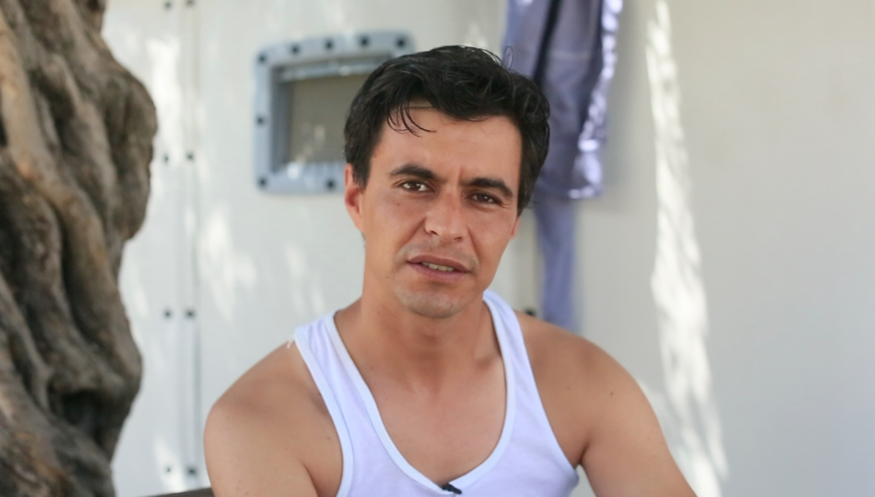 Mohammad Jouiet, from Morocco, sits in front of his assigned unit in Kara Tepe transit camp on Lesbos island, where he will remain until his asylum application is heard or he is deported under the terms of the E.U.–Turkey deal. The details of the process remain unclear and the legal conditions of return murky. (Iason Athanasiadis)