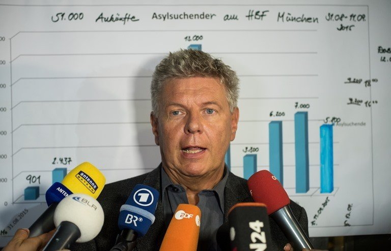 Munich's mayor Dieter Reiter gives a press statement at the central train station in Munich, Germany. In the background, the statistics read that from Aug. 31, to Sept. 11, 2015 around 51,000 asylum seekers arrived in the city. (Nicolas Armer/dpa via AP)