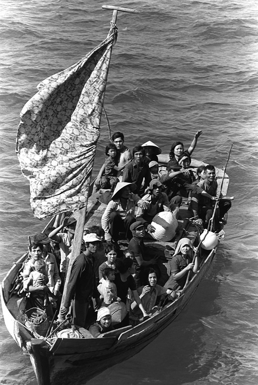 A boat with 35 Vietnamese refugees, waiting to be taken on board a U.S. naval vessel after spending eight days at sea. (Wikimedia Commons/Phil Engman)